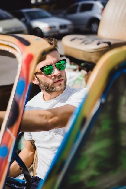 Jeune homme à lunettes de soleil dans un cabriolet Photo gratuit