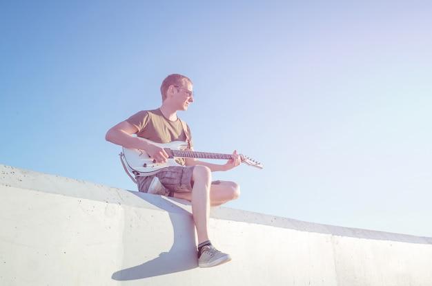 Un jeune homme à lunettes de soleil avec une guitare est assis sur le fond d'un ciel sans nuages. Photo Premium
