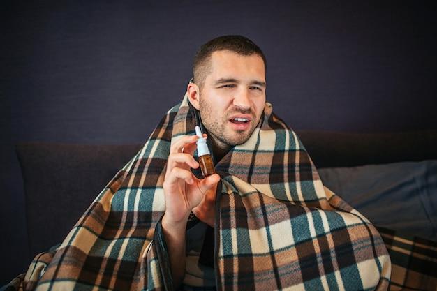 Un Jeune Homme Malade Et Malade Tient Un Spray Nasal Dans Les Mains. Il Rétrécit Mais Regarde La Caméra. Guy Va éternuer. Il A L'air Mauvais. L'homme Est Assis Dans La Chambre. Photo Premium