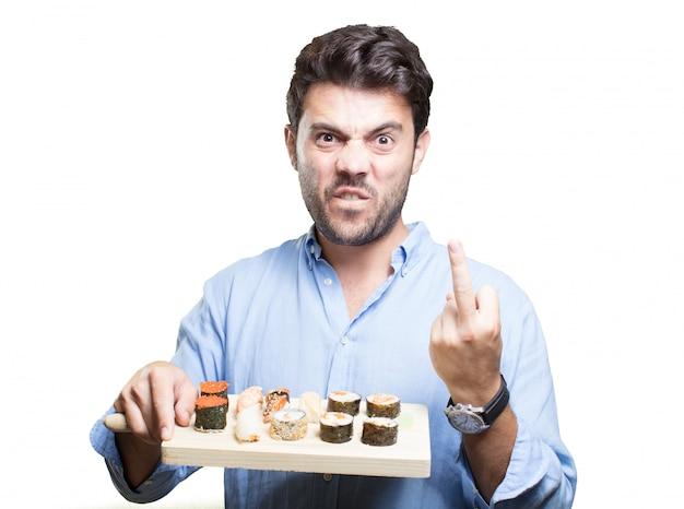 Jeune homme manger des sushis sur fond blanc Photo Premium
