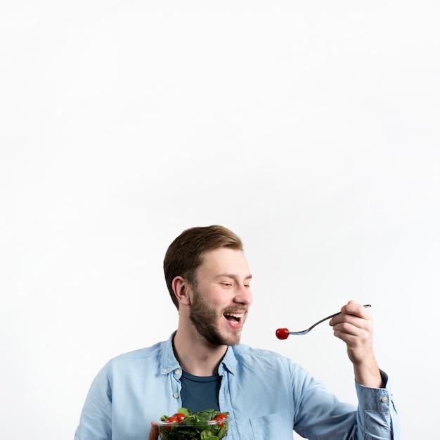 Jeune homme, manger, tomate cerise rouge, et, salade, dans, fond blanc Photo gratuit