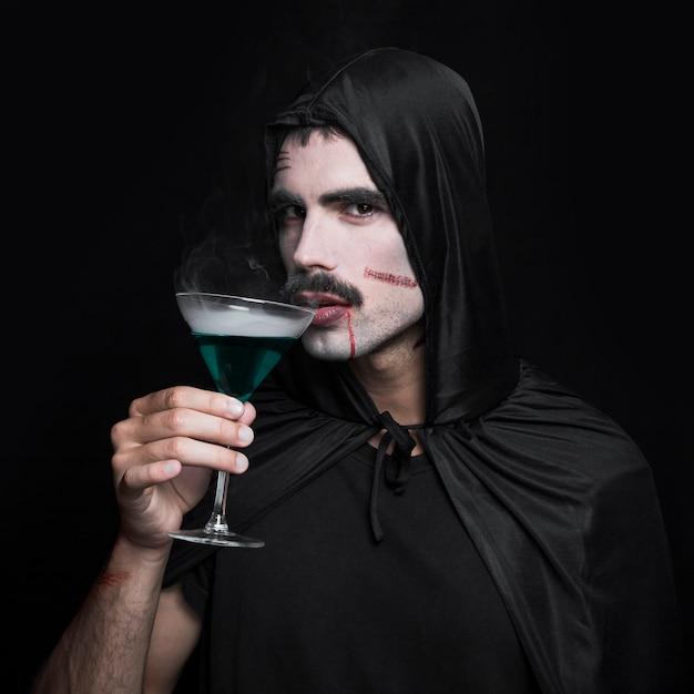 Jeune homme en manteau d'halloween noir posant en studio avec un verre de liquide vert Photo gratuit