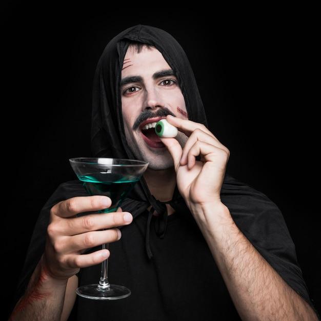Jeune homme en manteau noir qui pose en studio avec des yeux et des boissons artificiels Photo gratuit