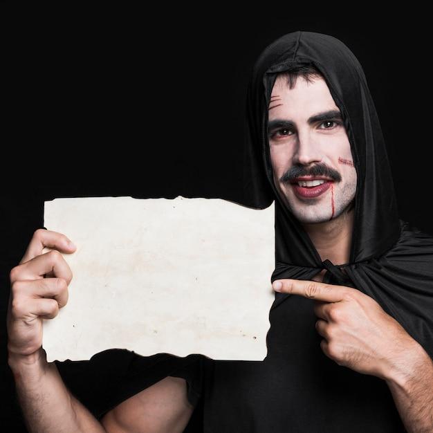 Jeune homme en manteau noir et t-shirt posant en studio avec un morceau de papier vierge Photo gratuit