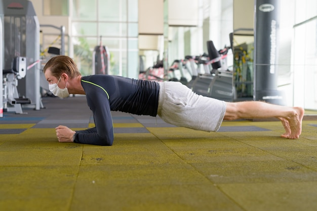 Jeune Homme Avec Masque Faisant La Position De La Planche Sur Le Sol Au Gymnase Pendant Le Coronavirus Covid-19 Photo Premium