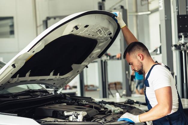 Jeune homme mécanique vérifiant la voiture Photo gratuit