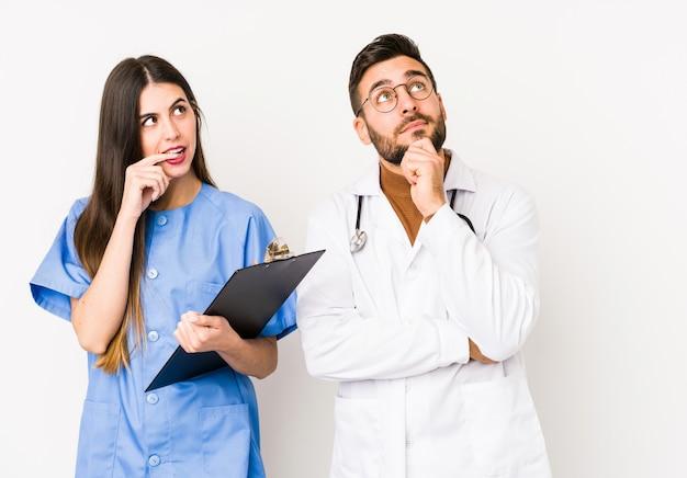 Jeune Homme Médecin Et Une Infirmière Se Sont Détendus En Pensant à Quelque Chose En Regardant Un Espace Vide. Photo Premium