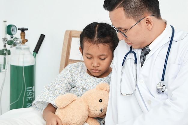 Jeune homme médecin pédiatre vérifiant fille Photo Premium