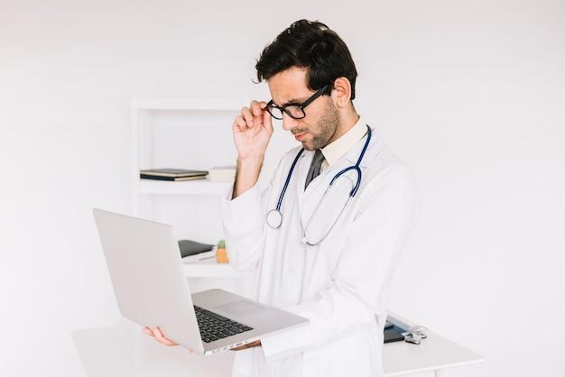 Jeune homme médecin portant des lunettes à la recherche à l'écran d'ordinateur portable Photo gratuit