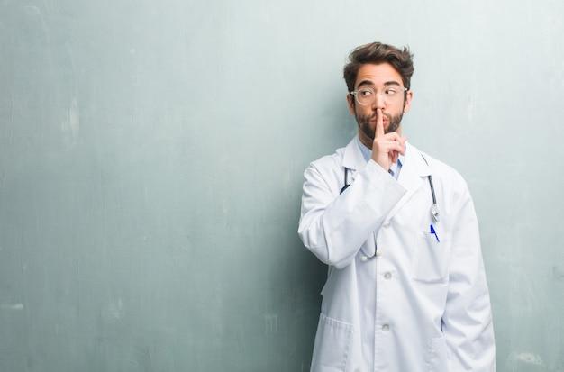 Jeune homme médecin sympathique contre un mur de grunge avec un espace de copie gardant un secret Photo Premium