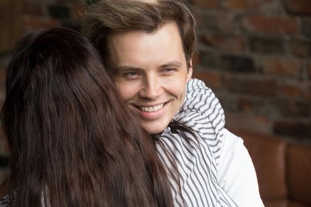 Jeune homme menteur sournois souriant joyeusement pendant que la femme l'embrasse Photo gratuit