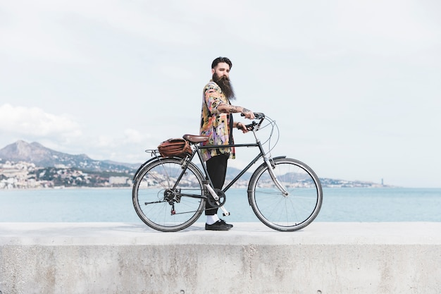 Jeune homme à la mode avec son vélo debout sur le brise-lames près de la côte Photo gratuit