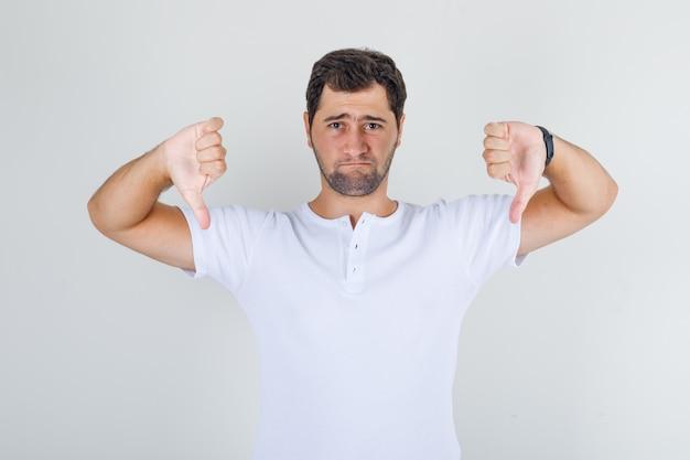 Jeune Homme Montrant Les Pouces Vers Le Bas En T-shirt Blanc Et à La Triste Photo gratuit