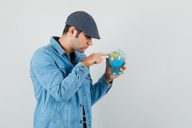 Jeune Homme Montrant Quelque Part Sur Mini Globe En Veste, Casquette Et à La Recherche Concentrée. Vue De Face. Photo gratuit