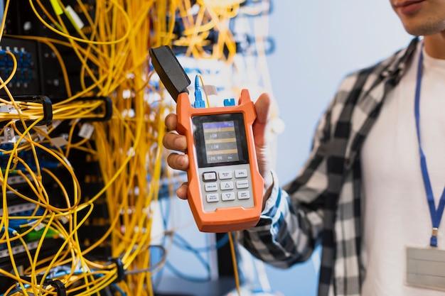Jeune homme montrant un testeur de fibre optique Photo gratuit