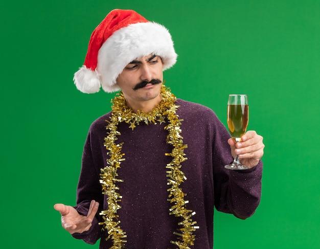 Jeune Homme Moustachu Portant Chapeau De Père Noël Avec Des Guirlandes Autour Du Cou Tenant Un Verre De Champagne En Le Regardant Avec Une Expression Confuse Debout Sur Fond Vert Photo gratuit