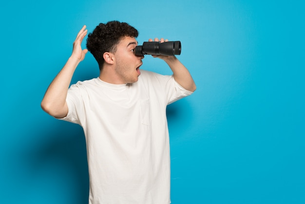 Jeune Homme Sur Un Mur Bleu Et Regardant Au Loin Avec Des Jumelles Photo Premium