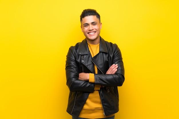 Jeune homme sur un mur jaune isolé, gardant les bras croisés en position frontale Photo Premium