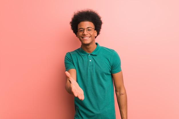 Jeune Homme Sur Un Mur Rose Tendre La Main Pour Saluer Quelqu'un Photo Premium