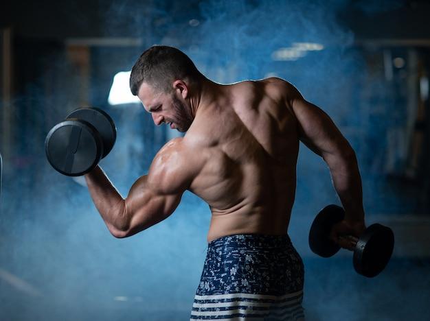 Jeune homme musclé, entraînement avec haltères. guy entraîne son biceps Photo Premium