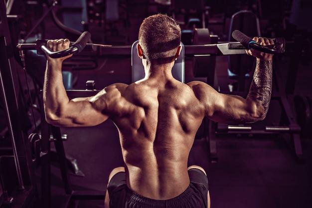 Jeune Homme Musclé, Faire Des Exercices Difficiles Avec Des Haltères Pour Deltas Moyens Des épaules Dans La Machine De Formation Au Gymnase Photo Premium