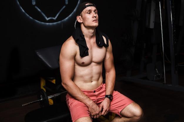 Jeune homme musclé et torse nu au repos dans la salle de sport pendant l'entraînement, montrant le torse musclé, les pectoraux et les abdominaux, assis sur un banc Photo Premium