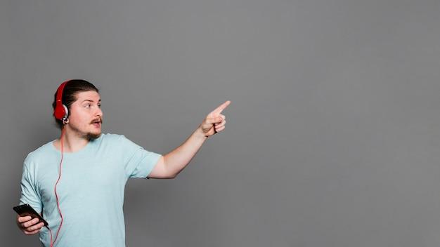 Jeune homme, musique écoute, sur, casque, par, téléphone portable, pointage doigt, contre, mur gris Photo gratuit