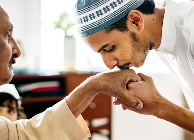 Jeune homme musulman faisant preuve de respect envers son père Photo gratuit