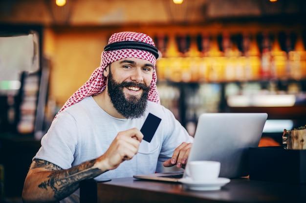 Jeune Homme Musulman Tatoué Barbu Positif Souriant Assis Dans Un Café, Tenant Une Carte De Crédit Et à La Recherche De Quelque Chose à Acheter En Ligne. Photo Premium
