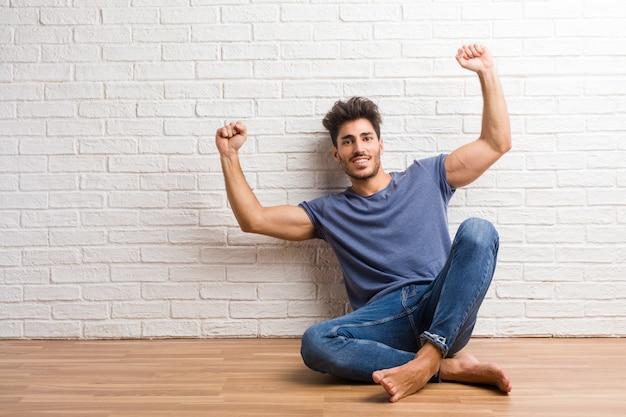 Jeune homme naturel assis sur un plancher en bois très heureux et excité, levant les bras Photo Premium