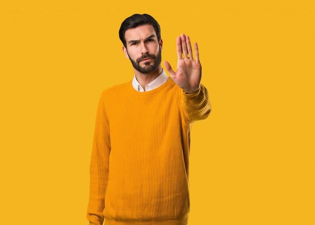 Jeune homme naturel mettant la main devant Photo Premium