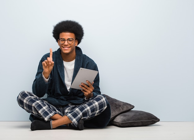 Jeune homme noir assis sa maison et tenant sa tablette montrant numbere Photo Premium