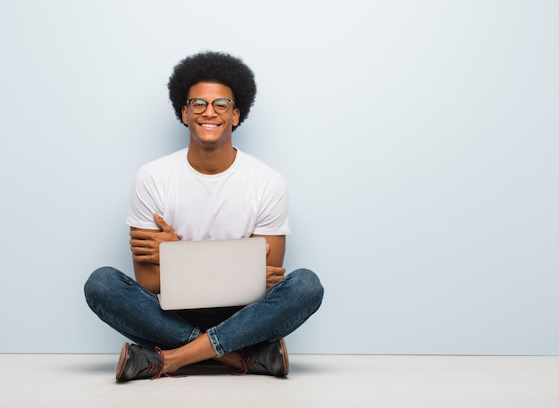 Jeune homme noir assis sur le sol avec un ordinateur portable croisant les bras, souriant et détendu Photo Premium
