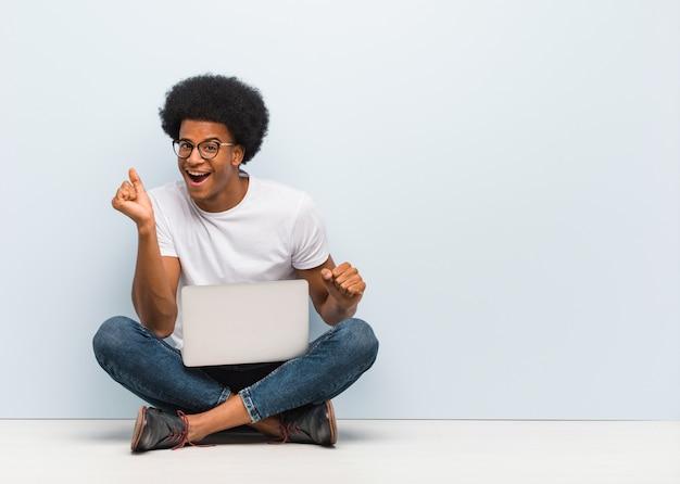 Jeune homme noir assis sur le sol avec un ordinateur portable qui danse et s'amuse Photo Premium