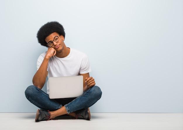 Jeune homme noir assis sur le sol avec un ordinateur portable en train de penser à quelque chose, regardant sur le côté Photo Premium