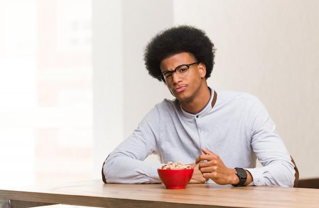 Jeune homme noir ayant un petit déjeuner traversant les bras détendu Photo Premium