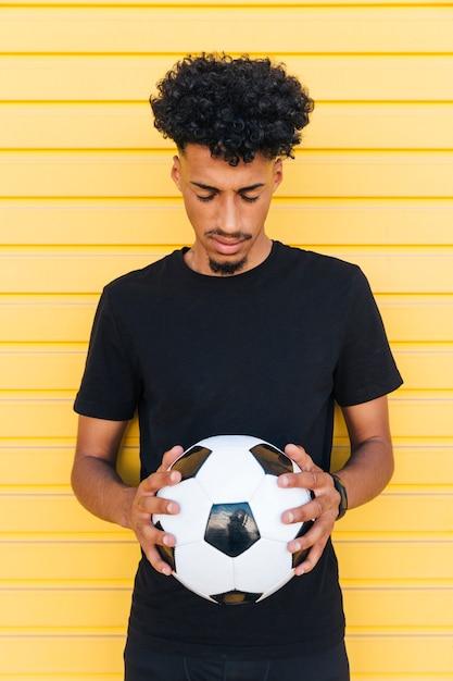 Jeune homme noir avec ballon de foot fermé les yeux Photo gratuit