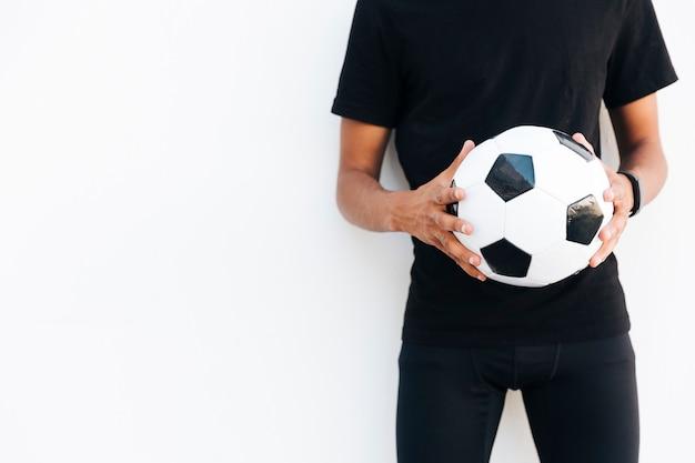Jeune homme noir en noir avec ballon de foot Photo gratuit