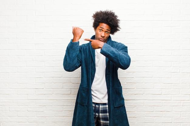 Jeune homme noir portant un pyjama avec une robe à la recherche d'un air impatient et fâché montrant la montre demandant la ponctualité veut être à l'heure contre le mur de briques Photo Premium