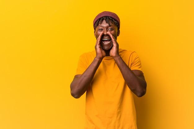 Jeune homme noir portant des rastas sur fond jaune en criant excité à l'avant. Photo Premium