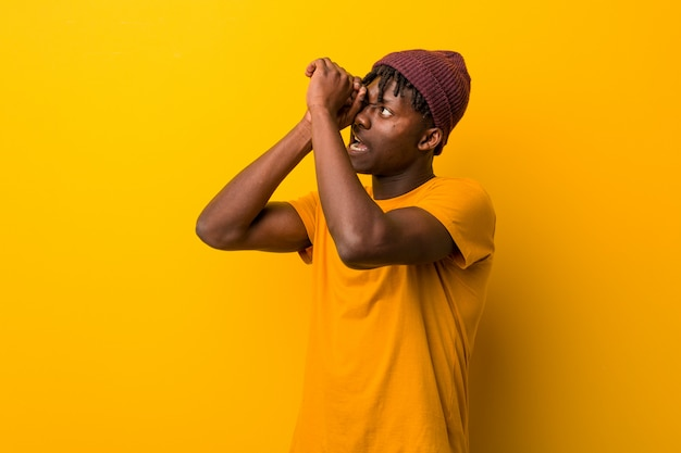 Jeune homme noir portant des rastas sur fond jaune, regardant au loin, le tenant la main sur le front. Photo Premium