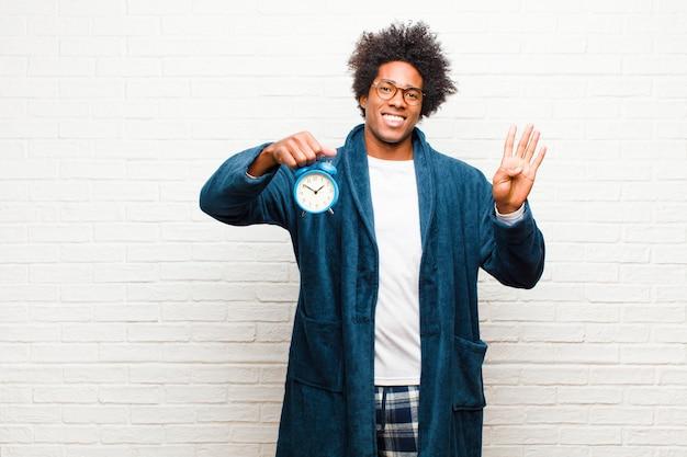 Jeune homme noir en pyjama avec réveil Photo Premium