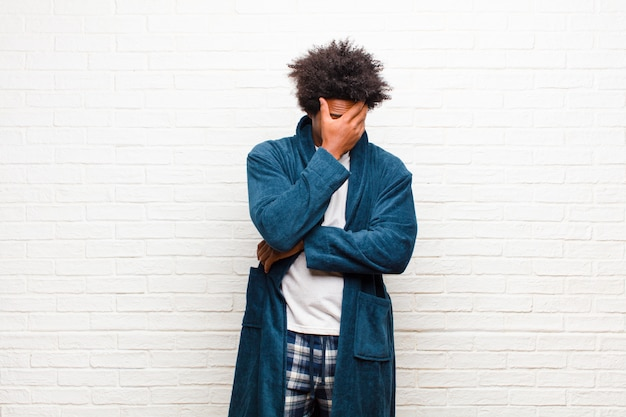 Jeune homme noir en pyjama avec une robe à l'air stressé, honteux ou contrarié, avec un mal de tête couvrant le visage avec un mur de briques à la main Photo Premium