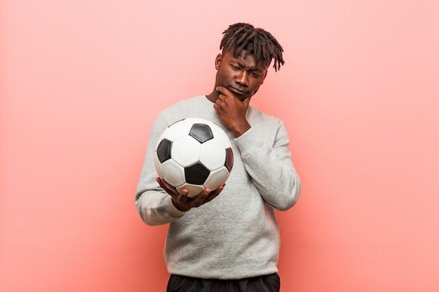 Jeune homme noir de remise en forme tenant un ballon de football à la recherche sur le côté avec une expression douteuse et sceptique. Photo Premium