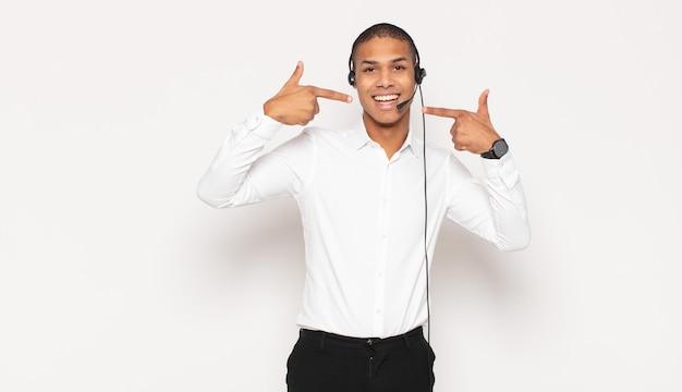Jeune Homme Noir Souriant Avec Confiance En Montrant Son Large Sourire, Attitude Positive, Détendue Et Satisfaite Photo Premium