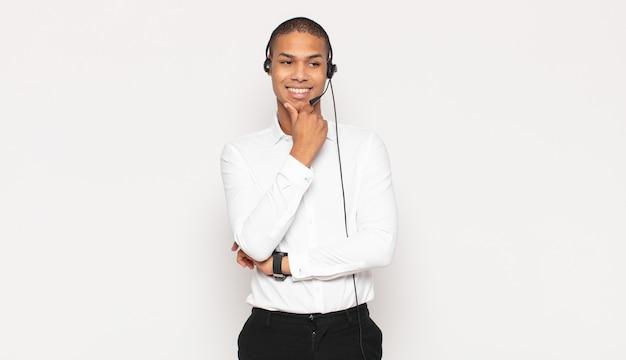 Jeune Homme Noir Souriant Avec Une Expression Heureuse Et Confiante Avec La Main Sur Le Menton, Se Demandant Et Regardant Sur Le Côté Photo Premium