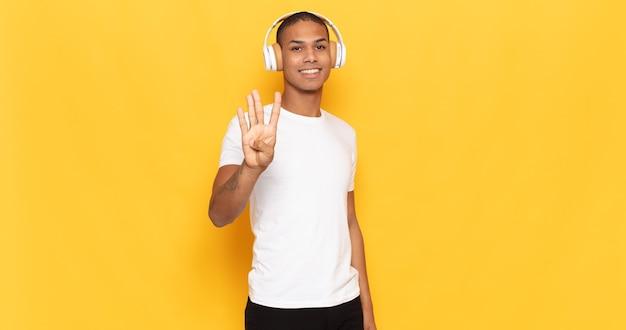 Jeune Homme Noir Souriant Et à La Recherche Amicale, Montrant Le Numéro Quatre Ou Quatrième Avec La Main En Avant, Compte à Rebours Photo Premium