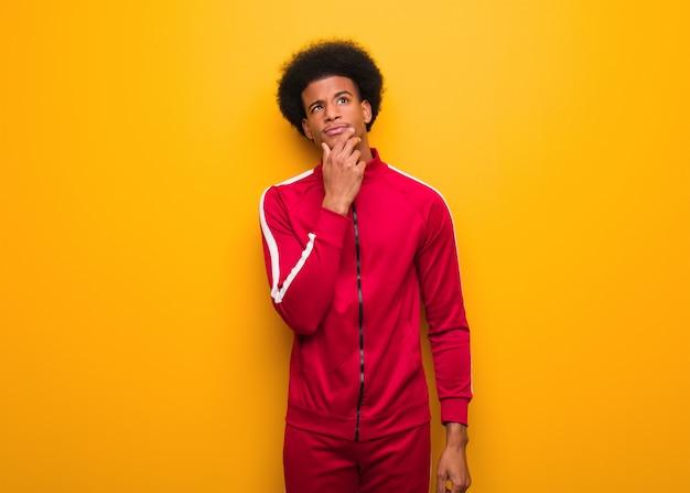 Jeune homme noir sportif sur un mur orange doutant et confus Photo Premium