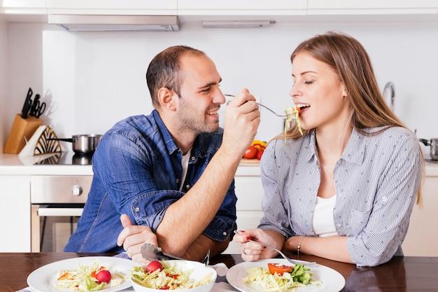 Jeune homme nourrit sa salade à sa femme assise dans la cuisine Photo gratuit