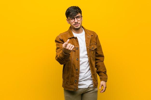 Jeune Homme Occasionnel Hispanique Pointant Du Doigt Sur Vous Comme Si Vous Invitiez à Vous Rapprocher. Photo Premium